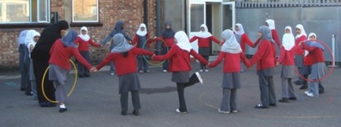 photo of school children in a circle on school grounds