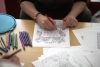 photo of a person colouring in a sheet of paper